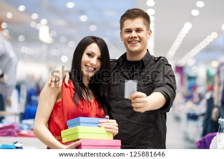 Happy young couple spending money at clothing store - stock photo