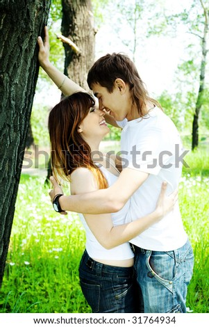 happy young couple spending time in summer park - stock photo
