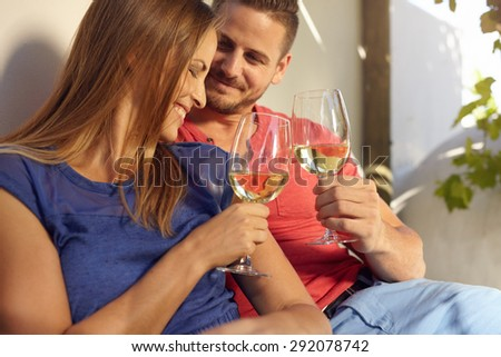 Happy young couple spending time in their backyard and enjoying a glass of wine. Smiling man and woman celebrating with wine, toasting wine glasses outdoors. - stock photo