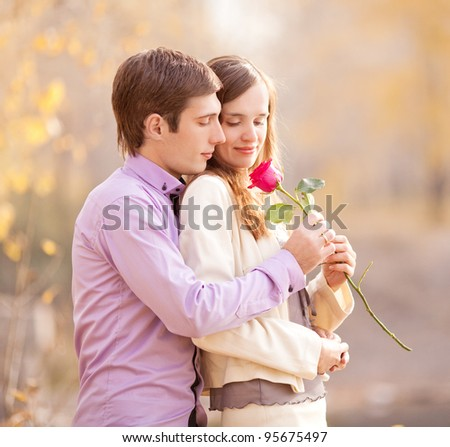 happy young couple spending time outdoor in the autumn park (focus on the man) - stock photo