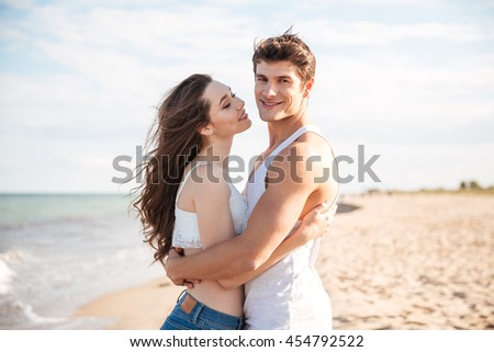 Happy young couple standing and embracing on the beach - stock photo