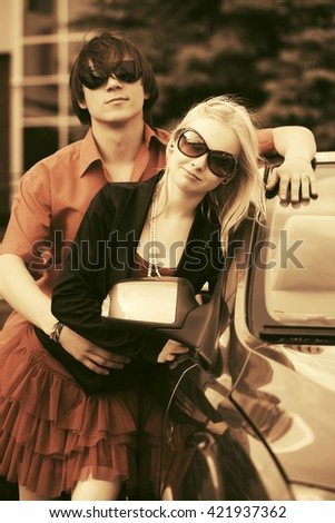 Happy young couple standing by new car - stock photo
