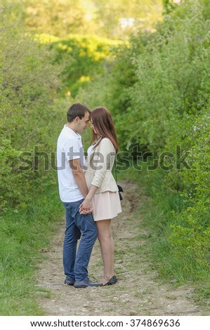 Happy young couple standing close to each other in park - stock photo