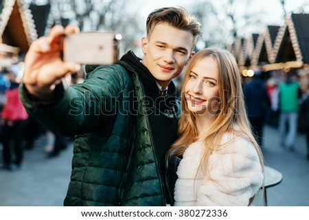 Happy young couple standing close to each other in warm coats, holding mobile phone and doing selfie, smiling, Christmas fest at background. - stock photo