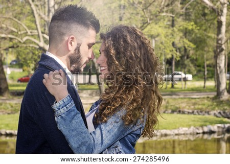 Happy young couple standing in the park on a  spring day .  - stock photo