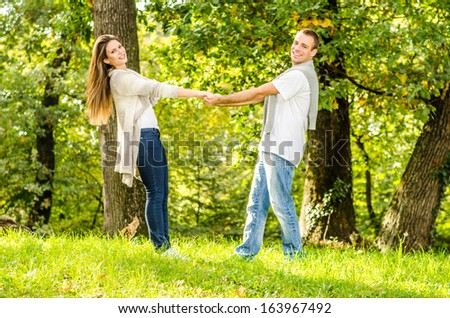 Happy young couple standing on a meadow and enjoying the autumn nature in the park - stock photo