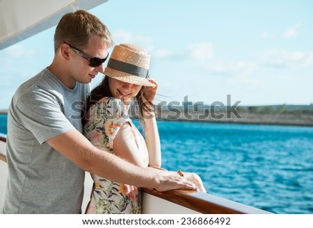 Happy young couple standing on the ship board - stock photo