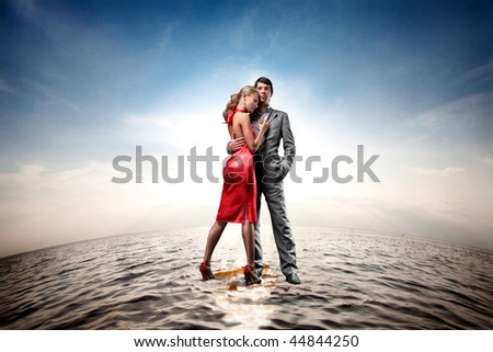 Happy young couple standing on water - stock photo