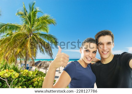 Happy, young couple taking a self portrait photo, selfie, at the tropical beach - stock photo