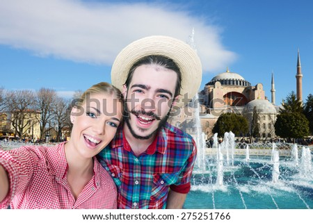 Happy, young couple taking a self portrait photo, selfie in front of Aya Sofia mosque  in Istanbul, Turkey - stock photo