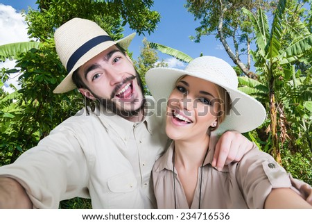 Happy, young couple taking a self portrait photo, selfie, in the jungle.Safari clothing. - stock photo