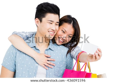 Happy young couple taking a selfie on white background - stock photo