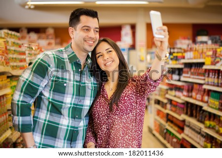 Happy young couple taking a selfie with a smart phone while shopping at the supermarket - stock photo