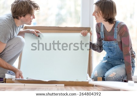 Happy young couple taking delight in putting together self assembly furniture as they move into their new house. - stock photo