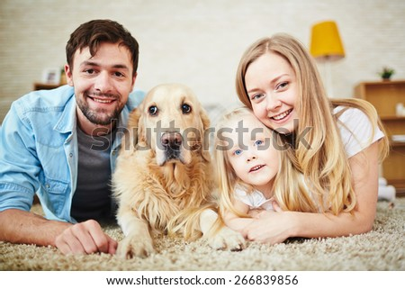 Happy young couple, their daughter and dog
