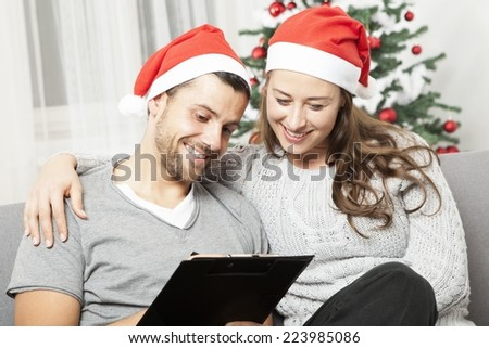 happy young couple think about to do list for christmas eve on sofa