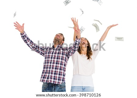 Happy young couple throwing currency notes in air on white background - stock photo