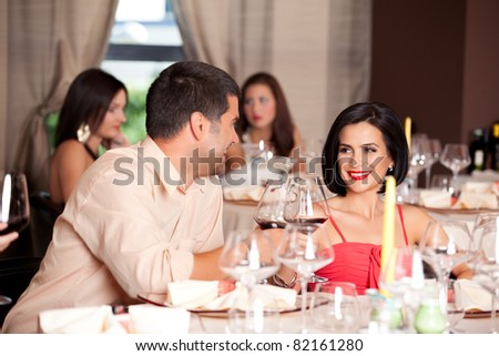 happy young couple toasting restaurant table - stock photo