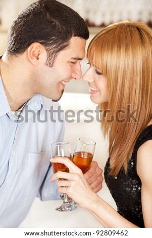 Happy young couple toasting their anniversary with champagne at home ambient - stock photo