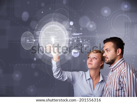 Happy young couple touching abstract high technology circular buttons - stock photo