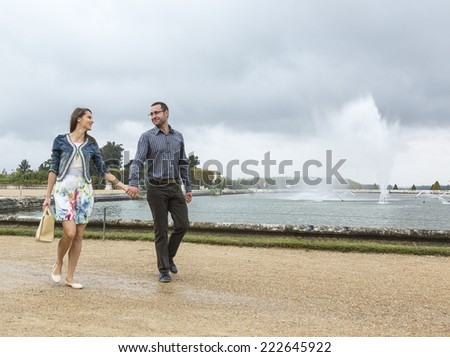 Happy young couple walking hand in hand in a French garden near a big fountain.
