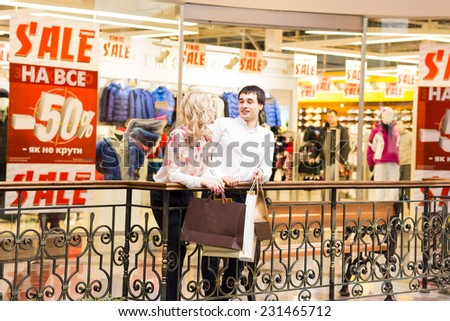 Happy young couple walking in the mall carrying shopping bags