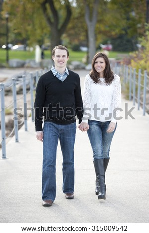 Happy young couple walking on the pier on a sunny day.