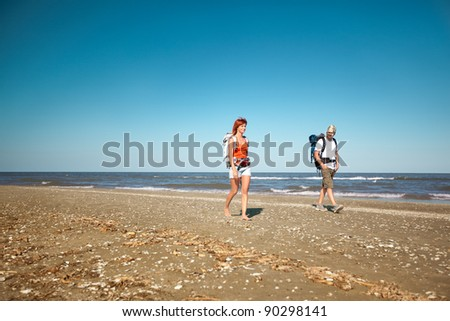 happy, young couple walking together on a deserted beach, wearing backpacks