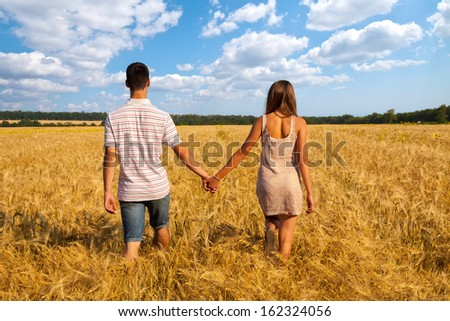 Happy young couple walking together  through wheat field - stock photo