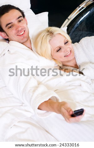 happy young couple watching tv in bed - stock photo