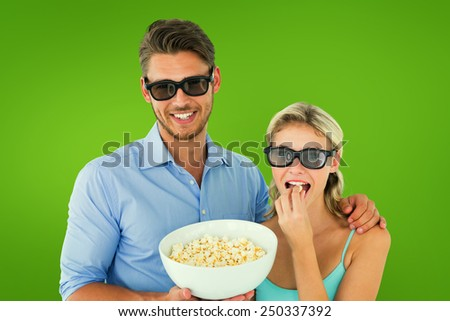 Happy young couple wearing 3d glasses eating popcorn against green vignette - stock photo