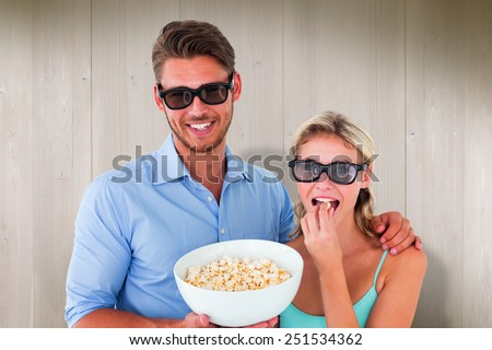Happy young couple wearing 3d glasses eating popcorn against wooden planks - stock photo