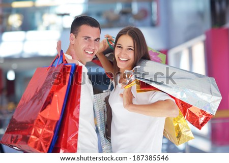 happy young couple with bags in shopping centre mall - stock photo