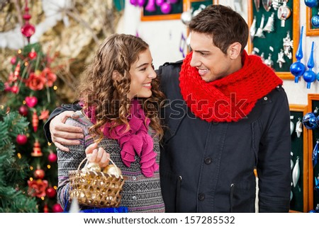 Happy young couple with bauble basket looking at each other in Christmas store - stock photo