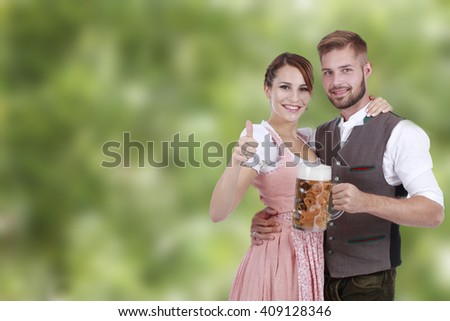 Happy young couple with beer and traditional costume in front of green background