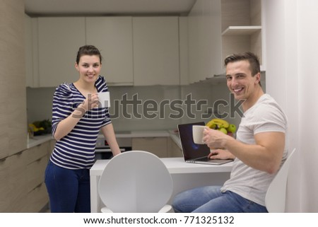 happy young couple with laptop computer enjoying morning coffee in modern kitchen at home