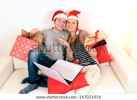 Happy young couple with laptop online shopping Christmas presents
