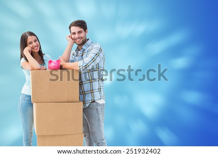 Happy young couple with moving boxes and piggy bank against valentines heart design - stock photo