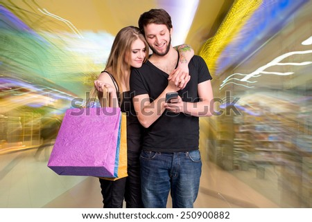 Happy young couple with shopping bags looking at mobile phone on a blue background - stock photo