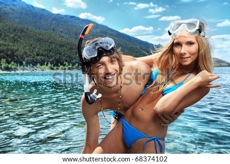Happy young couple with snorkelling gear standing on a sea beach. - stock photo
