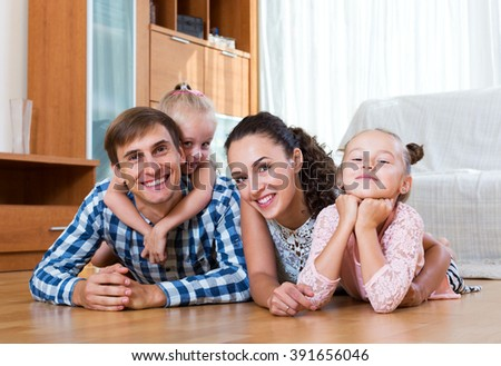 Happy young couple with two little daughters relaxing at home - stock photo