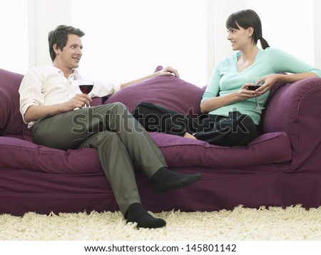 Happy young couple with wineglasses relaxing on sofa
