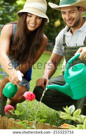 Happy young couple working in the garden, watering rose. - stock photo