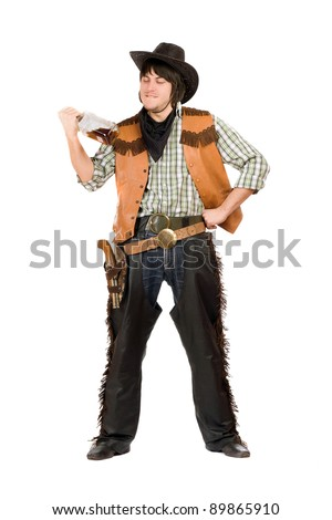 Happy young cowboy with a bottle of whiskey in hand - stock photo