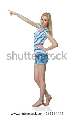 Happy young denim girl in shorts standing casually in full length, pointing to the side at blank copy space, against white background - stock photo