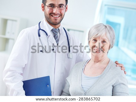 Happy young doctor and elderly female patient - stock photo