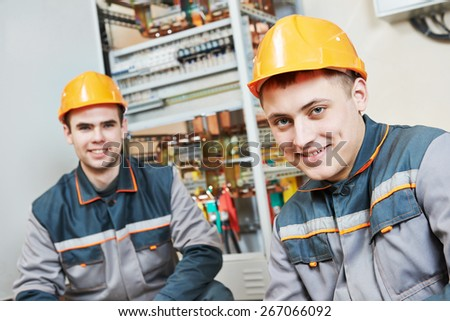 Happy young electrician builder workers in front of fuseboard - stock photo