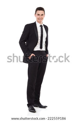 Happy young elegance man standing with hands in pockets. Full length studio shot isolated on white. - stock photo