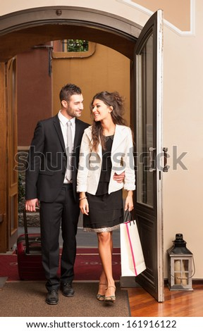 Happy young elegant couple entering in hotel. - stock photo