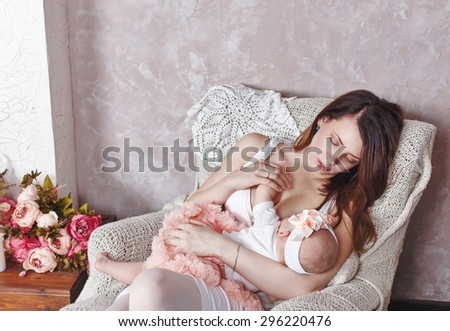 Happy young family, a mother breastfeeds little daughter. The concept of happiness of motherhood. - stock photo